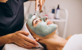 cosmetologist-applying-mask-face-client-beauty-salon_1303-16759